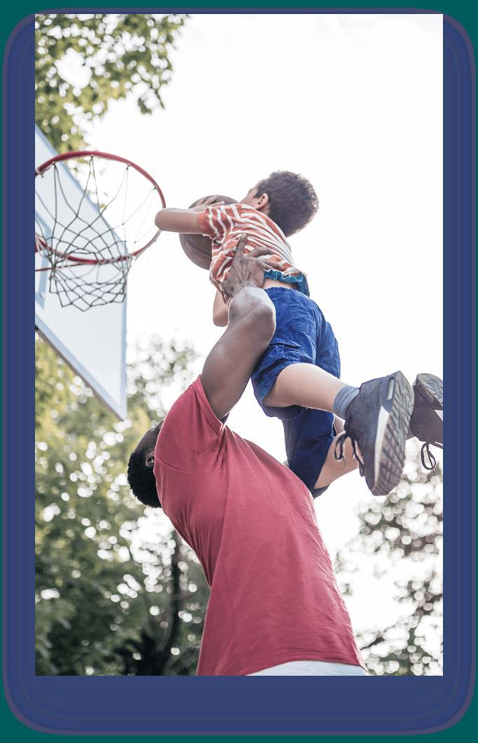 man lifting kid with basketball to basketball hoop