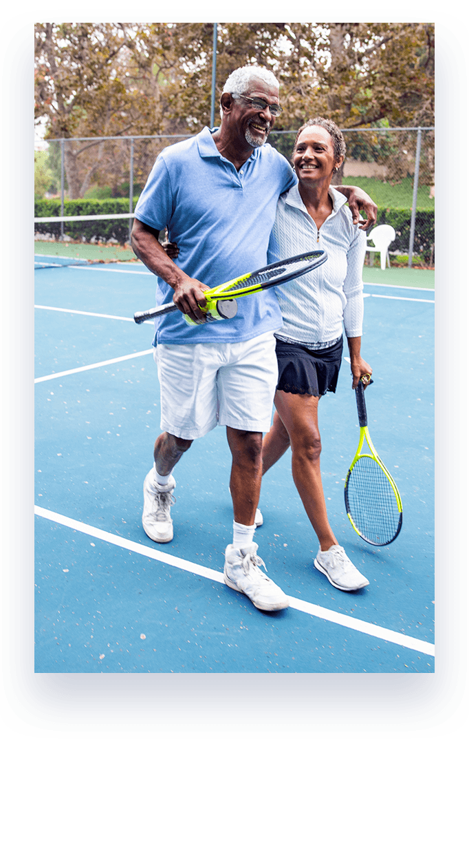 couple walking on tennis court with tennis rackets